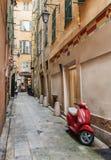 在狭窄的街道在尼斯,法国上的红色滑行车 库存照片