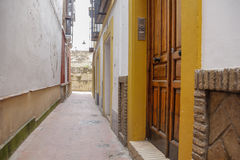 在狭窄的街道的木门 库存照片