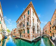 在狭窄的运河在五颜六色的房子之间,威尼斯,意大利的传统长平底船 图库摄影