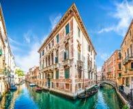 在狭窄的运河在五颜六色的房子之间,威尼斯,意大利的传统长平底船 免版税库存照片