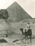 在狮身人面象和金字塔的骆驼乘驾 免版税库存照片