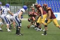 在狼和蓝色龙之间的橄榄球比赛 免版税库存图片