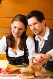 在猎人客舱吃的年轻夫妇 免版税库存图片