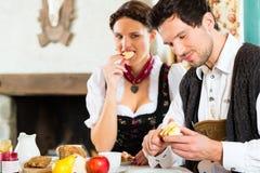 在猎人的客舱吃的年轻夫妇 免版税库存照片