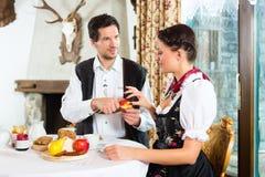在猎人的客舱吃的年轻夫妇 免版税库存图片