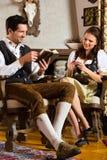 在猎人的客舱或高山小屋的年轻夫妇 免版税库存图片