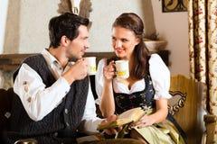 在猎人的客舱饮用的茶的年轻夫妇 免版税库存照片