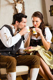 在猎人的客舱饮用的茶的年轻夫妇 库存图片