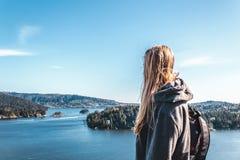 在猎物岩石顶部的背包徒步旅行者女孩在北温哥华区, BC,加州 免版税库存图片