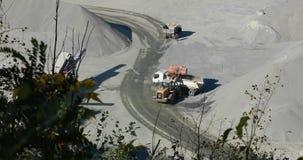 在猎物的一台推土机倾吐货物入卡车,装载翻斗车在猎物 股票录像