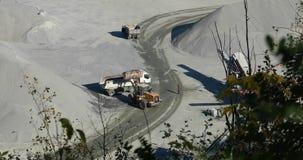 在猎物的一台推土机倾吐货物入卡车,装载翻斗车在猎物 影视素材