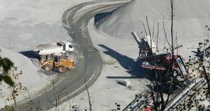 在猎物的一台推土机在猎物装载一块石头入翻斗车的身体,一黄色budozer工作,装载转储 影视素材