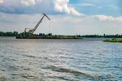 在猎物的巨大的挖掘者沙子提取采矿的在湖 免版税图库摄影