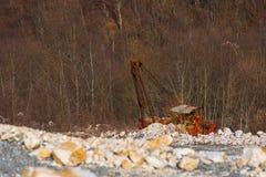 在猎物的老打破的被放弃的生锈的挖掘机 免版税库存照片