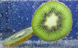 在猕猴桃段的泡影在蓝色背景的苏打水 免版税库存图片