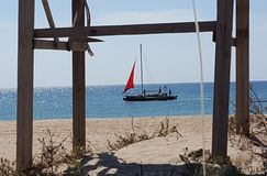 在猩红色风帆下的小船向海 免版税库存图片