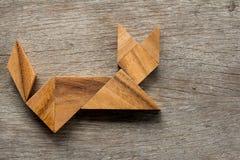 在猫坐的形状的中国七巧板难题在木背景 图库摄影