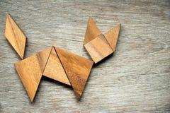 在猫形状的七巧板难题在木背景 免版税库存图片