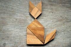 在猫形状的七巧板难题在木背景 免版税图库摄影