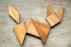 在猫形状的七巧板难题在木背景 库存照片