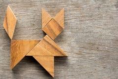 在猫形状的中国七巧板难题在木背景 库存图片