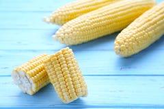 在玉米棒的新鲜的玉米在一张蓝色木桌上 库存照片