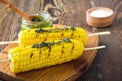 在玉米棒的烤玉米用在木板的pesto调味汁 库存照片
