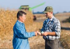 在玉米以后收获的愉快的农夫  库存图片