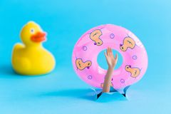 在玩偶武器储备可膨胀的水池浮游物旁边的橡胶鸭子和涌现从蓝纸背景 淹没最小的创造性的abst 图库摄影