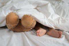 在玩具熊脚旁边的亚洲小孩脚在白色床、板料和枕头上 免版税库存照片
