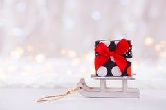 在玩具白色雪撬的一点俏丽的礼物盒在轻的bokeh backgrou 免版税图库摄影
