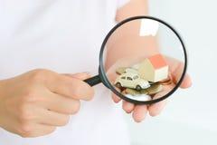 在玩具的房子和建议的汽车前面的放大镜家庭投资 库存照片