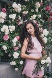 在玫瑰中的少妇在庭院里 免版税库存图片