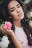 在玫瑰中的少妇在庭院里 免版税图库摄影