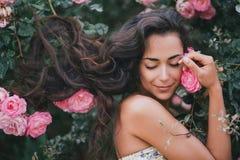 在玫瑰中的少妇在庭院里 库存图片