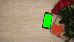 在玫瑰和礼物盒附近的智能手机在木背景,送货服务 影视素材