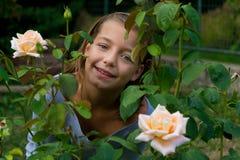 在玫瑰愉快微笑之间的小吉普赛儿童女孩 库存图片