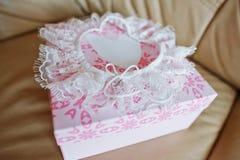 在玫瑰色箱子的白色婚礼袜带在皮革沙发 图库摄影