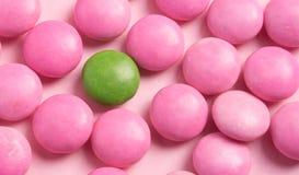 在玫瑰色背景的颜色糖果 免版税库存照片