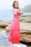 在玫瑰色褂子的美好的岸上金发碧眼的女人流行性deathes 免版税库存图片