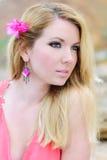 在玫瑰色褂子的美好的岸上金发碧眼的女人流行性deathes 免版税图库摄影