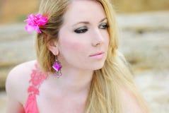 在玫瑰色褂子的美好的岸上金发碧眼的女人流行性deathes 库存照片