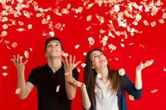 在玫瑰色雨下的夫妇。 免版税库存图片