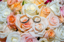在玫瑰花束的婚戒  免版税库存照片