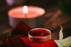 在玫瑰花瓣和蜡烛背景的婚戒 免版税库存照片