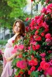 在玫瑰附近的红头发人怀孕的womann 免版税图库摄影