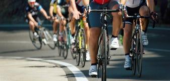 在环公路比赛期间,有赛跑的骑自行车者骑自行车 库存图片