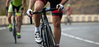 在环公路比赛期间,有赛跑的骑自行车者骑自行车 免版税库存照片