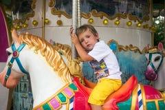 在环形交通枢纽的疲乏的小男孩骑马 免版税库存图片