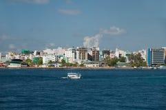 在环礁Kaafu,马尔代夫的首都的同一个海岛上的男性城市,前景的一条小船在海 免版税库存图片
